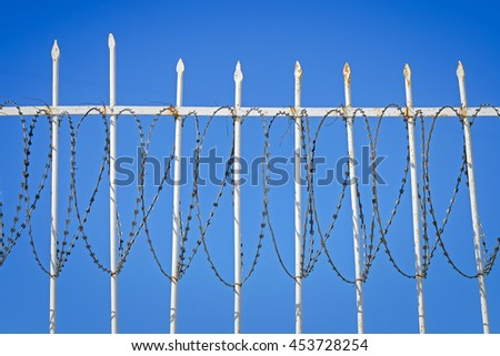 White iron fence with a barbed wire against the blue sky - stock photo