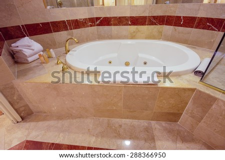 White jacuzzi bathtub and brass taps decorated with marble tiles  - stock photo