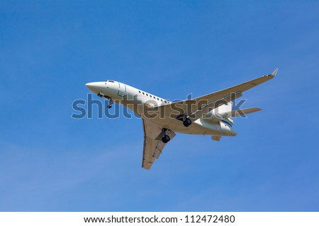 white jet passenger aircraft with the gear against the blue sky - stock photo