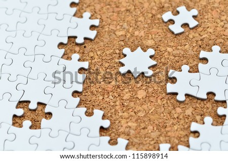 White jigsaw puzzle. (Mount in cork board) - stock photo