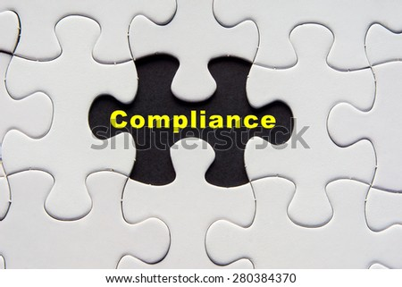 White jigsaw puzzle with a written word Compliance in yellow - stock photo