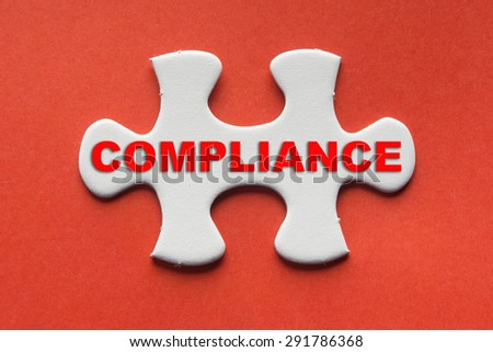 White jigsaw puzzle with a written word Compliance on a red background. - stock photo