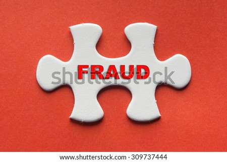 White jigsaw puzzle with a written word Fraud on a red background. - stock photo
