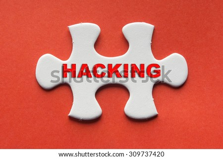 White jigsaw puzzle with a written word hacking on a red background. - stock photo
