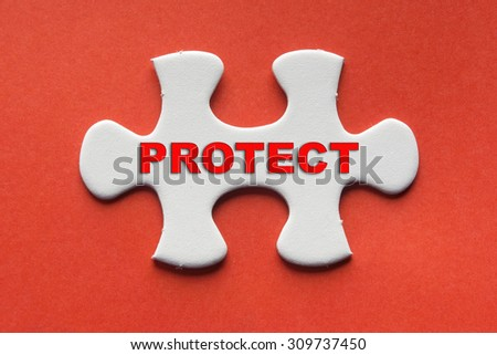 White jigsaw puzzle with a written word protect on a red background. - stock photo