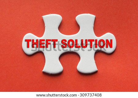 White jigsaw puzzle with a written word theft solution on a red background. - stock photo