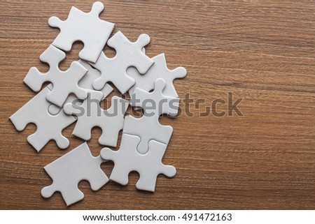 white jigsaw puzzles scattered on the floor of wooden planks