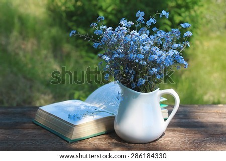 White jug with bouquet of forget-me-nots on  wooden table and the opened book - stock photo