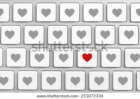 White keyboard with an icon of red heart on the buttons - stock photo