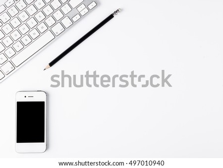 White keyboard with black pencil and phone on desk on white background