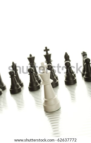 White King in the foreground against a background of black army chips - stock photo