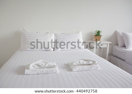 white king size bed, two pillows, towel and tree pot plant in bedroom for rest and relax, feel comfortable - stock photo