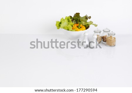 white kitchen background with bowl of vegetable and seasoning bottles - stock photo