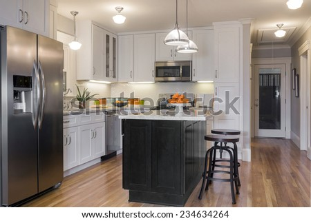 White Kitchen in Modern Home with white Marble counter tops, wooden floor, bat chairs and all new appliances. - stock photo