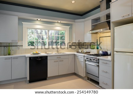 White Kitchen in traditional Home with granite counter tops wooden floor and all new new stainless steel appliances. - stock photo