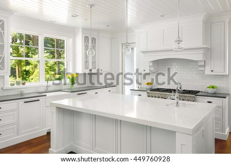 White kitchen interior with island, sink, cabinets, and hardwood floors in new luxury home with lights off
