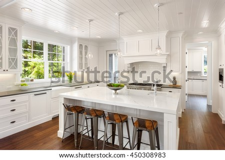 White Kitchen Interior with Island, Sink, Cabinets, and Hardwood Floors in New Luxury Home with Lights On. Includes Window View of Lush Exterior