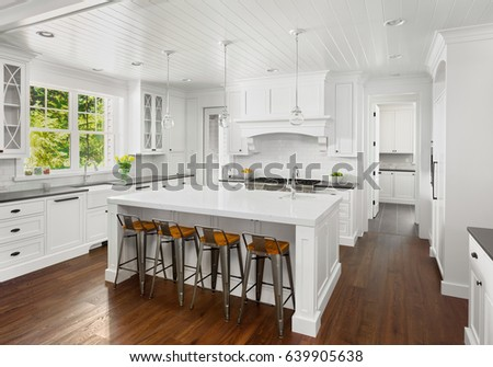 White Kitchen Interior with Island, Sink, Cabinets, and Hardwood Floors in New Luxury Home, with Lights Off