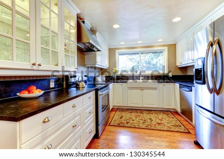 White kitchen interior with large sink, window, hardwood floor. - stock photo