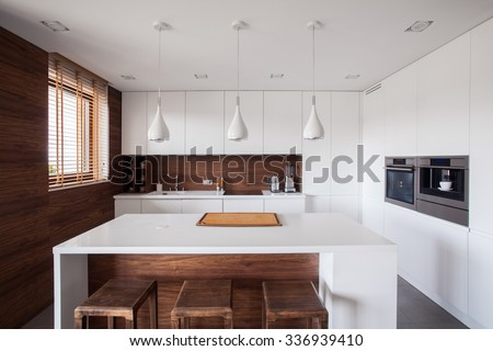 White kitchen island in modern and wooden kitchen - stock photo
