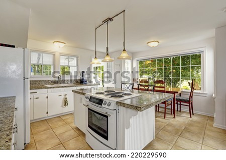 White kitchen room with granite tops. Kitchen island with built-in stove. View of dining area with large window