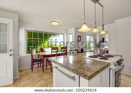 White kitchen room with granite tops. Kitchen island with built-in stove. View of dining area with large window - stock photo