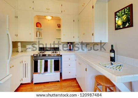 White kitchen with beige walls and cherry hardwood floor.