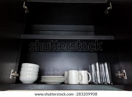 White kitchenware in black cupboard, closeup - stock photo
