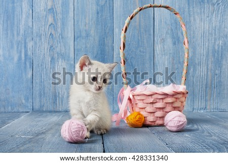 White kitten with pink wool ball and straw basket.  - stock photo