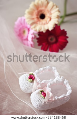 White knit baby booties decorated with flowers and ribbons with gerberas in the background - stock photo