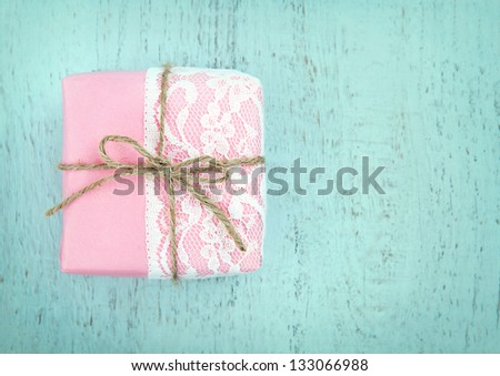White lace and a simple bow on pink gift box on light blue wooden vintage background - concept for a girl's birthday or for mother's day - stock photo