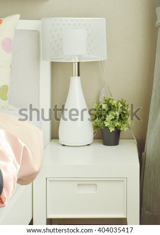 White lamp and flower pot on bedside table next to bed