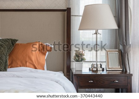 white lamp with vase of plant and picture frame on wooden table side in luxury bedroom design - stock photo