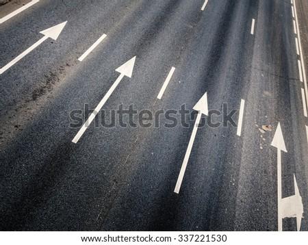 White lane marker arrows contrasted against dark grey asphalt highway - stock photo