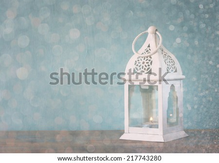 white lantern over wooden table and glitter lights background.  - stock photo