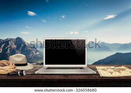 white laptop map hat rope torch on the table with mountains in the background mock up presentation