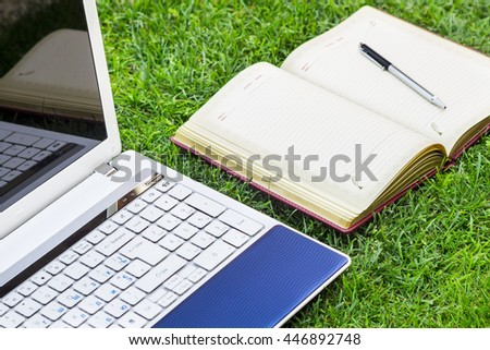 White Laptop, notebook and pen Placed On Green Grass Field.