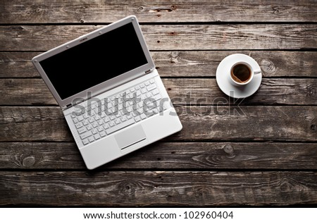 White laptop with coffee cup on old wooden table. - stock photo