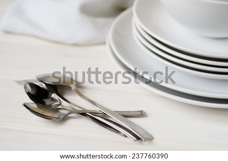 white large and small plates and bowls on a light table - stock photo