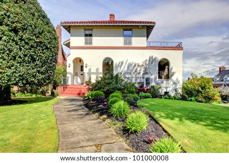 White large Spanish style house with front door and walkway. - stock photo