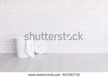 White laundry basket standing in spacious room with light flooring and brick wall - stock photo