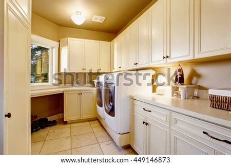 White laundry room interior with tile floor and cabinets. House interior.