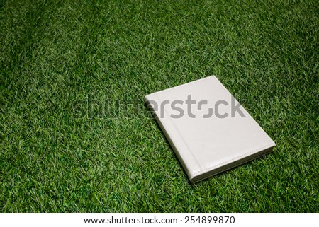White leather book lying on the grass