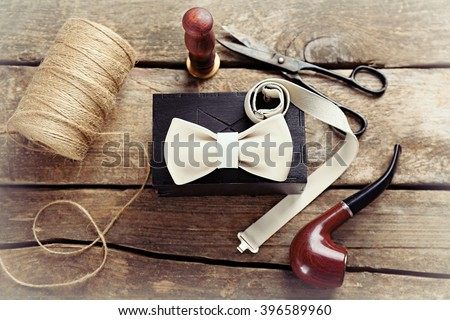White leather bow tie and black gift box with crafts and tobacco pipe on wooden table, top view - stock photo