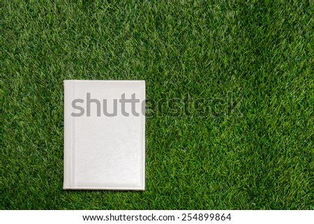 White leather empty book lying on the grass