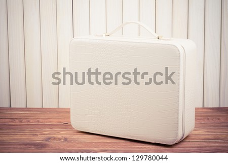 White leather travel suitcase on wood vintage photo - stock photo