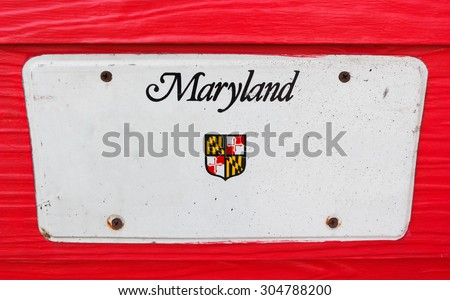 White license plate of Maryland, America on red wooden background. - stock photo