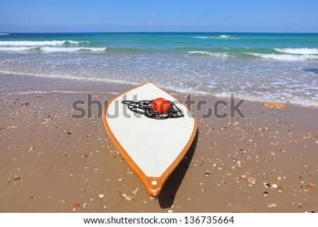 White lifeguard surf board with res buoy on the beach - stock photo
