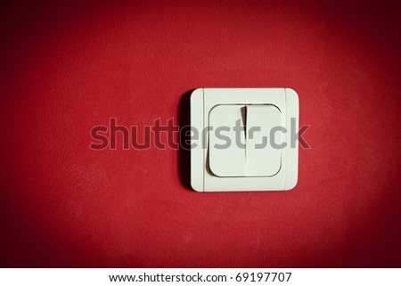 white light switch on red wall - stock photo