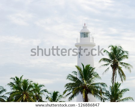 White lighthouse above palm tops on cloudy sky background, Galle Sri Lanka